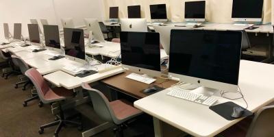 Photo of computers on desks.